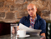 Morning coffee and news. Handsome young man reading newspaper in a bae and drinking coffee Stock Image