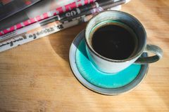 Morning coffee and newspapers. View of a cup of black coffee and stack of newspapers on a wooden table illuminated with rays of sun coming from a window. Good royalty free stock photo