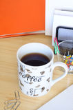 Morning coffee at office. A cup of coffee on desk, with some office equipment, vertical frame stock photo