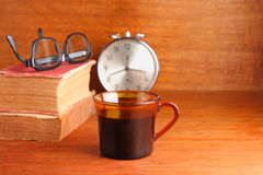 Morning coffee with old book. Cup of black coffee with alarm clock and old book on wood background Stock Photos