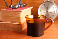 Morning coffee with old book. Cup of black coffee with alarm clock and old book on wood background Stock Image