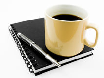 Morning coffee and pen on black notebook. Isolated on white stock photo