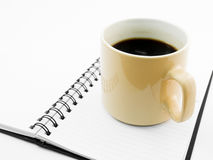 Morning coffee and pen on open black notebook. Isolated on white royalty free stock photos