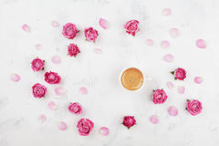 Morning coffee, petals and beautiful pink rose flowers on white stone table top view in flat lay style. Cozy breakfast. Stock Photo