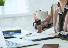 Morning coffee before a productive working day. Young female oficce worker holding coffee cup and looking at the laptop royalty free stock images