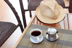Morning coffee served in vietnam coffee filter on rattan table with two rattan chairs Royalty Free Stock Image