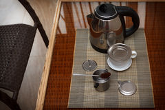 Morning coffee served in vietnam coffee filter on rattan table with two rattan chairs Stock Image