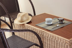 Morning coffee served in vietnam coffee filter on rattan table with two rattan chairs Stock Photos