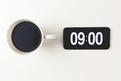 Morning coffee with time display on digital clock on mobile phon Royalty Free Stock Image
