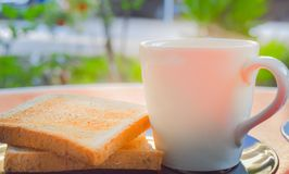 Morning coffee and toasted whole wheat bread on black plate on the red table with smoke over the cup of coffee in the sunshine. Royalty Free Stock Images