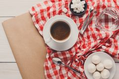 Morning coffee with treats on stylish checkered tablecloth on wh. Morning coffee at restaurant. White porcelain cup of black bitter coffee with treats on stylish Stock Photography