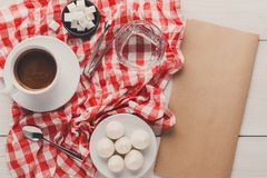 Morning coffee with treats on stylish checkered tablecloth on wh. Morning coffee at restaurant. White porcelain cup of black bitter coffee with treats on stylish Stock Images