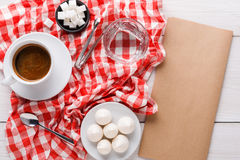 Morning coffee with treats on stylish checkered tablecloth on white background. Morning coffee at restaurant. White porcelain cup of black bitter coffee with Stock Photos