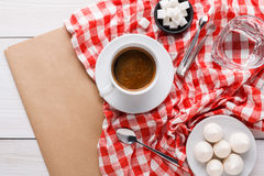 Morning coffee with treats on stylish checkered tablecloth on white background. Morning coffee at restaurant. White porcelain cup of black bitter coffee with Royalty Free Stock Photos