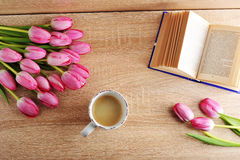 Morning coffee with tulips and reading books - the top view on w