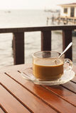 Morning coffee. Under the sunlight beside the sea Stock Photography