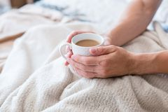 Morning coffee warmth man habit bed cup. Morning coffee warmth and energy. New day habit. Man in bed. Hands around white cup of latte royalty free stock photos