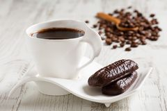 Morning coffee in white ceramic cup with wave shaped saucer and two cocoa biscuits on white wooden rustic table. Coffee beans in the distance Stock Image