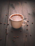 Morning coffee in a white cup on a brown table with flowers and cinnamon Royalty Free Stock Photo