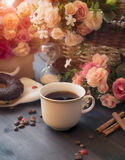 Morning coffee in a white cup on a brown table with flowers and cinnamon Stock Photos