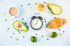 Morning coffee in a white cup Croissant Avocado Awakening with an alarm clock Breakfast cheerfulness, a healthy breakfast freshnes. S royalty free stock photos