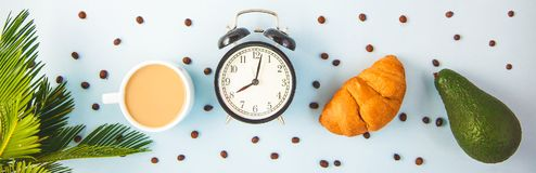 Morning coffee in a white cup Croissant Avocado Awakening with an alarm clock Breakfast cheerfulness, a healthy breakfast freshnes. S Banner concept royalty free stock photo