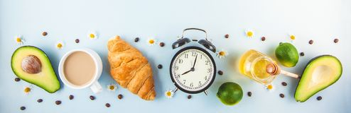 Morning coffee in a white cup Croissant Avocado Awakening with an alarm clock Breakfast cheerfulness, a healthy breakfast freshnes. S Copy space stock images