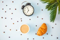 Morning coffee in a white cup Croissant Avocado Awakening with an alarm clock Breakfast cheerfulness, a healthy breakfast freshnes. S Flat lay stock image
