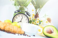 Morning coffee in a white cup Croissant Avocado Awakening with an alarm clock Breakfast cheerfulness, a healthy breakfast freshnes. S royalty free stock photography