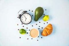 Morning coffee in a white cup Croissant Avocado Awakening with an alarm clock Breakfast cheerfulness, a healthy breakfast freshnes. Morning coffee in a white cup royalty free stock images
