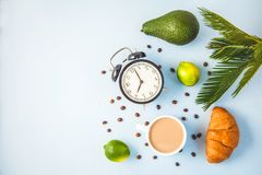Morning coffee in a white cup Croissant Avocado Lime on a light background Wake-up with an alarm clock Breakfast cheerfulness, a h. Ealthy breakfast freshness royalty free stock photography