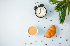 Morning coffee in a white cup Croissant on a light background Wake-up with an alarm clock Breakfast cheerfulness, a healthy breakf. Ast freshness Flat lay Copy royalty free stock photo