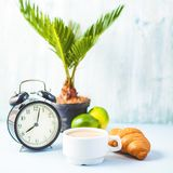 Morning coffee in a white cup Croissant on a light background Wake-up with an alarm clock Breakfast cheerfulness, a healthy breakf. Ast freshness Copy spase stock photos