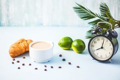 Morning coffee in a white cup Croissant Lime on a light background Wake-up with an alarm clock Breakfast cheerfulness, a healthy b. Reakfast freshness Copy spase stock photography