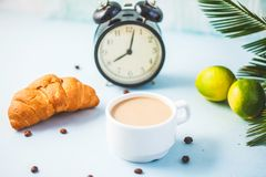 Morning coffee in a white cup Croissant Lime on a light background Wake-up with an alarm clock Breakfast cheerfulness, a healthy b. Reakfast freshness Close- up royalty free stock image