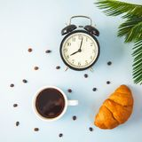 Morning coffee in a white cup Croissant Wake-up with an alarm clock Breakfast cheerfulness, a healthy breakfast freshness Flat lay.  royalty free stock image