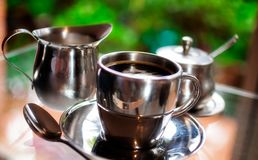 Morning Coffee in your garden. A hot cup of the morning coffee in a silver cup with pots of milk and sugar on a colorful garden bokeh blurred background Royalty Free Stock Photo