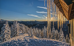 Icicles Fall From Roof at Sunrise in Cascade Mountains. The Corner of an Alpine Snow Hut Drips with Icicles that Glow with the Morning Sunrise in the Cascade Stock Photography
