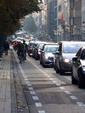 Morning commuters going to work by bicycle. BRUSSELS - OCTOBER 11: Morning commuters going to work by bicycle while the heavy car traffic is blocking the Royalty Free Stock Images