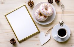 Morning composition with coffee and donuts  on a wooden table. Gold frame for the presentation of works or text. Royalty Free Stock Image