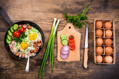 Morning cooking with fried eggs, sausages and vegetables. In pan on old wooden table Royalty Free Stock Photos