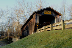 Morning covered bridge on rural river and woods Stock Image