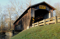 Morning covered bridge on rural river and woods Royalty Free Stock Image