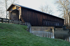 Morning covered bridge on rural river and woods Stock Photography