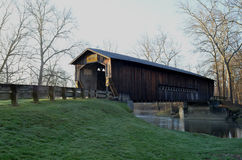 Morning covered bridge on rural river and woods Stock Photo