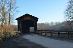 Morning covered bridge on rural river and woods Royalty Free Stock Photo