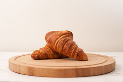 Morning croissants. Two freshly baked croissants placed one on top of each other on a wooden board that is resting on a rustic white painted kitchen table royalty free stock image