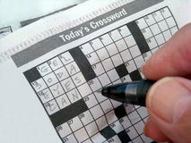 Morning Crossword Puzzle USA. Commuter starting daily newspaper crossword puzzle royalty free stock photo