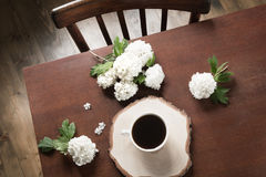 Morning cup of black coffee with flowers of viburnum in cafe. View from above. Royalty Free Stock Photography