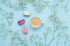 Morning cup of coffee, cake macaron and flower gypsophila on blue table from above. Cozy breakfast. Flat lay style. stock photos